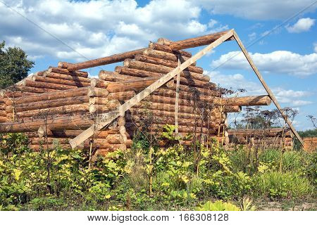 Construction of rural house from heavy logs on a background of blue sky with clouds. Horizontal photo