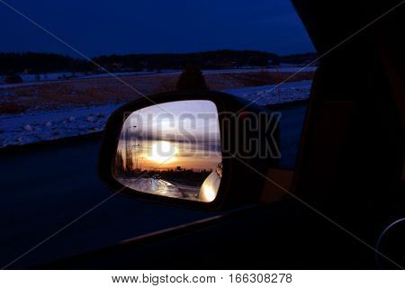 Sunset reflected in car side view mirror.