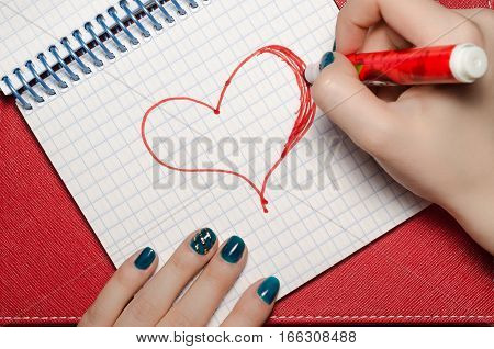 The girl draws a marker in a notebook heart Valentine's Day. Background red. Symbol of love, fourteen february.