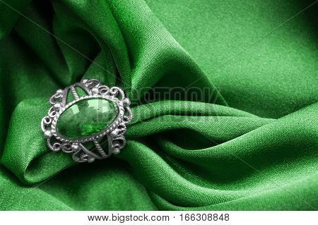 Vintage emerald ring on green crumpled satin closeup