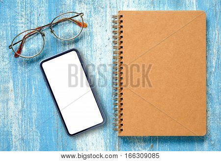 Smart phone with notebook and glasses on blue wooden floor.