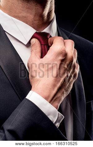 Partial view of businessman in black suit adjusting tie