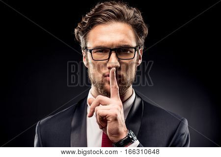 Handsome businessman in eyeglasses and suit gesturing for silence with finger