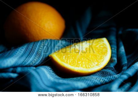 Orange and side of orange on linen with moody and dark style and background