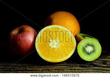 Orange kiwi and apple on wood plate with moody and dark style and background