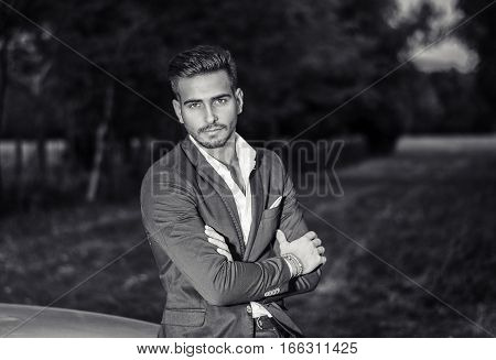 Portrait of young attractiave man in white shirt leaning on his new stylish polished car outdoor