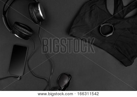 Flat lay of healthy concept with black color sport bra, earphone and smart on black background. Sport fashion, Sport accessories, top view, copyspace