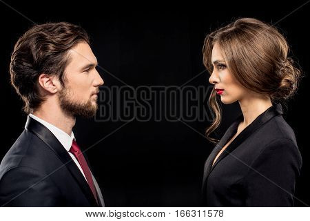 Serious couple in formal wear looking at each other on black