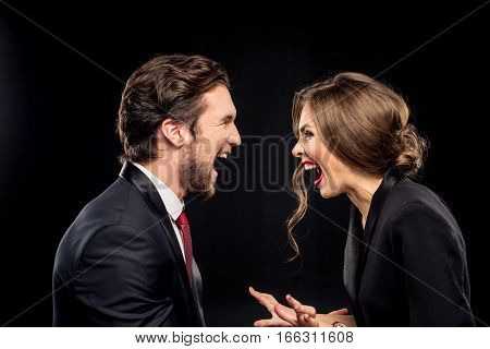 Laughing couple in formal wear looking at each other on black