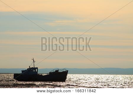 Beautiful view of the old fishing trawler at sunset