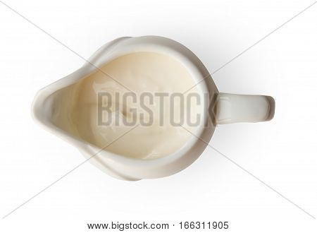 Closeup of white sauce, cream or mayonnaise in white sauceboat bowl isolated