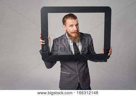 Hipster business man with beard and mustashes in suit looking through peeping out of frame, over grey background
