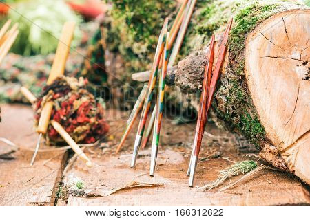 Various wooden needles and hooks next to wood log. Concept of eco style handicraft shop
