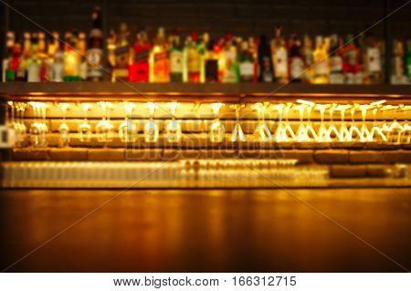 top of wood table with blur alcohol drinking bottle and glasses in the bar or pub at night background