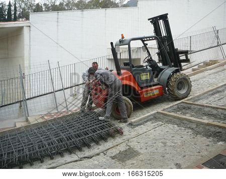 Workers Moving Steel Mesh Up Steep Hill