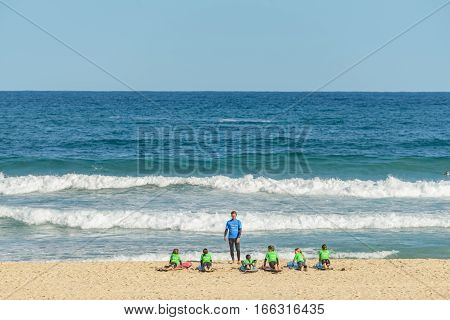 BONDI AUSTRALIA - OCTOBER 14 2016: A group of young people at a surfboard lesson in the world famous Bondi Beach in Sydney Australia.