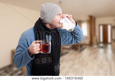 Man Drinking Hot Tea And Wiping Nose