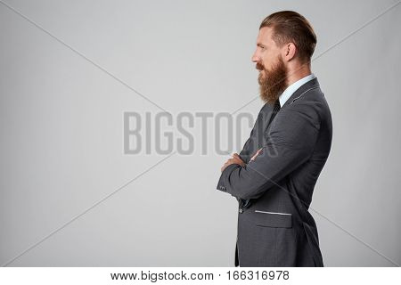 Side view of stylish business man with beard and mustashes in suit standing with folded hands looking forward over grey background
