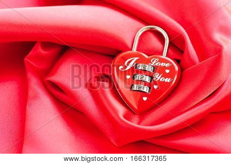 Padlock heart-shape on satin fabric background. Festive background