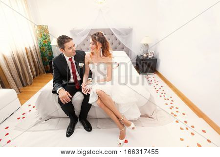 Newlyweds in bedroom. Loving. Love, tenderness. Just married. First night. On the floor there are red rose petals.