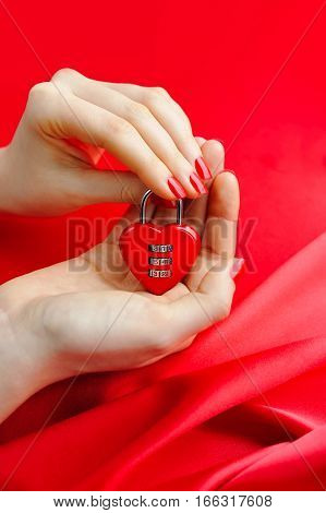 Padlock Heart-shape In Women's Hands Against A Background Of Red Silk