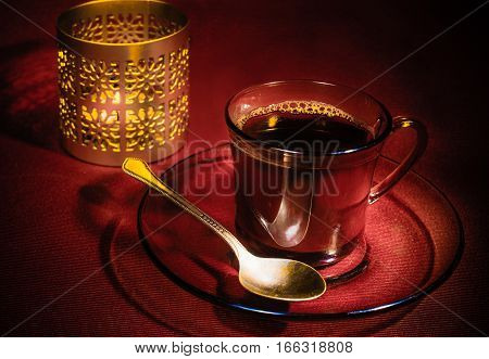 On Burgundy background: Cup brewed coffee on a transparent saucer lies a teaspoon next to the candle holder inside of which the candle burns.