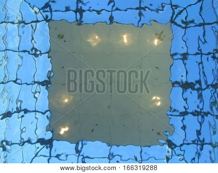 looking up through a clear glass covered skylight with water above