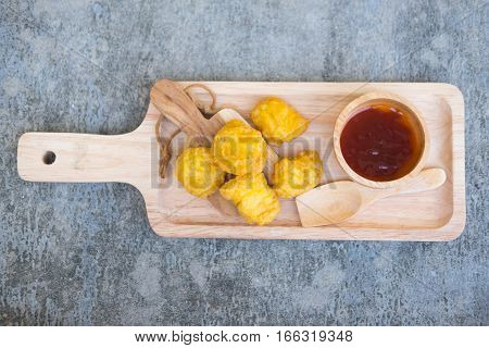 Tasty homemade chicken nuggets with ketchup on wood tray