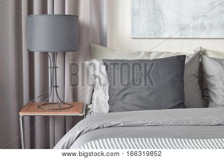 Black Pillow On Bed And Black Shade Lamp On Bedside Table
