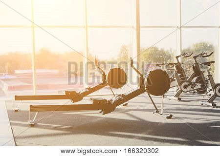 Modern gym interior with equipment. Fitness club with row of training leg exercise machines. Healthy lifestyle concept, evening backlight
