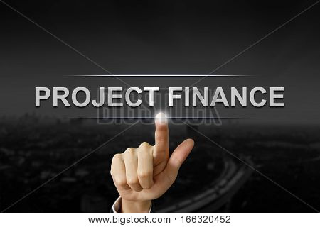 business hand clicking project finance button on black blurred background