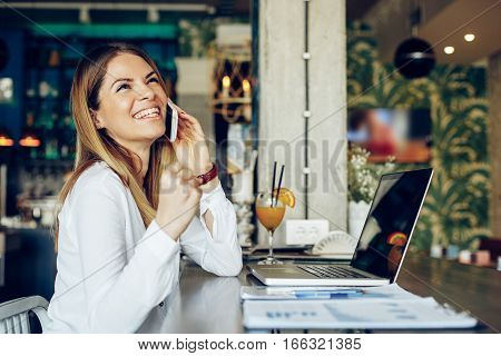 Young businesswoman talking on the phone and holding a clenched fist beside laptop on table in cafe