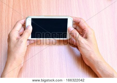 Woman hand holding and using smart phone on table wood