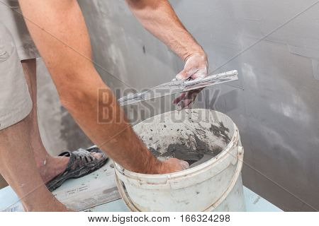 Man working with a metal spatula and prepared grout or adhesive when doing plaster