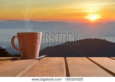Morning cup of coffee or tea with mountain background at sunrise
