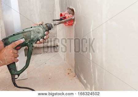 Electrician installing wall power socket plastic electrical junction box with drill