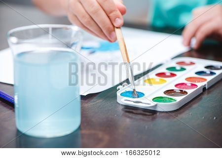 Close-up partial view of child drawing picture with watercolor paints