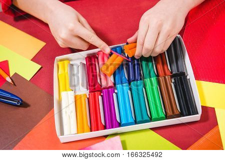 Partial view of schoolchild cutting colorful plasticine