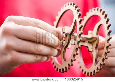 Partial view of kid holding wooden gear mechanical toy