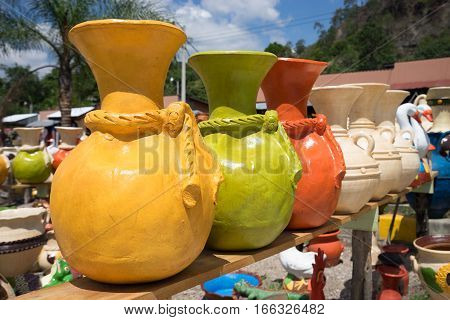 May 16 2016 Honduras: roadside pottery vendor stands with colourful clay artisan creations