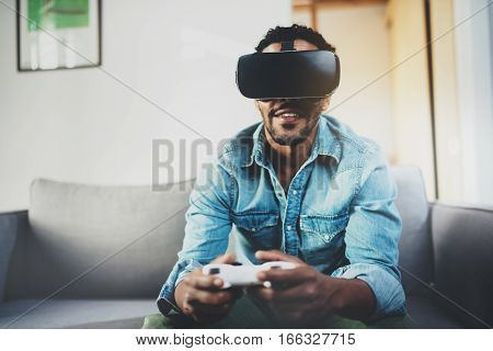 Attractive african man enjoying virtual reality glasses while sitting on sofa.Happy young guy with virtual reality headset or 3d glasses with controller gamepad playing video game at home.Blurred