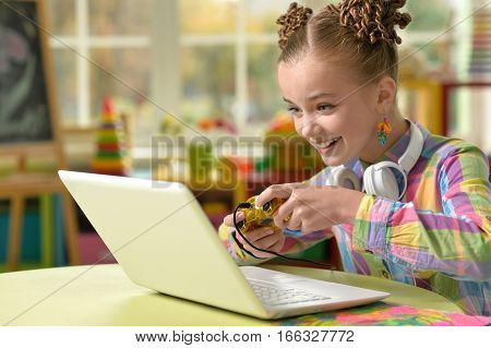 cute little girl playing computer games using laptop
