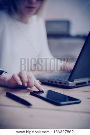 Closeup view of female finger touching black screen modern smartphone on the wooden table.Concept young business people using mobile devices at workplace.Vertical, film effect