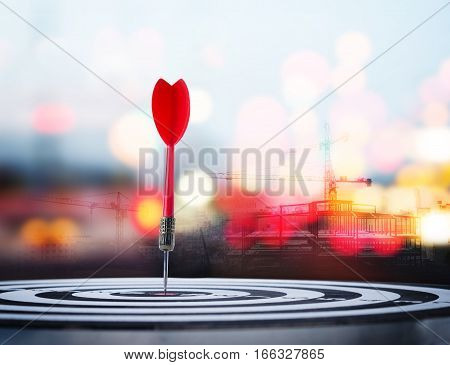 Close up shot red dart arrow on center of dartboard with construction and bokeh blur background metaphor to target success winner concept