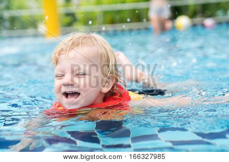 little baby boy with blond hair swimming in a pool in an inflatable vest.