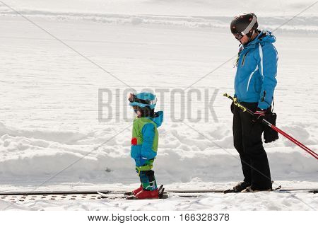 Ski trainer and little boy skiing downhill