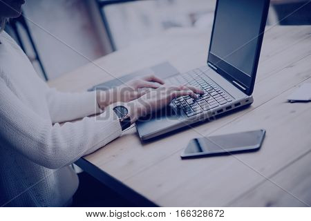 View young businesswoman working at laptop in office.Girl typing on keyboard while sitting her workplace.Horizontal, film effect, blurred background
