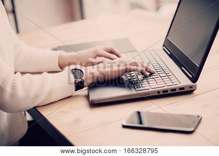 View young businesswoman working at laptop in office.Girl typing on keyboard while sitting her workplace.Horizontal, color filter, blurred background