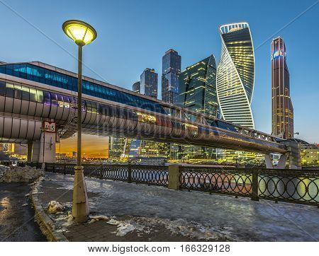 Moscow Russia - November 20 2016: Pedestrian bridge Bagration on the background of Moscow city from the embankment of Taras Shevchenko in the winter at dusk.