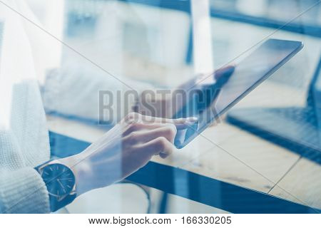 Closeup view of female hand touching display digital tablet at the wooden table.Concept young business people using mobile devices.Double exposure, skyscraper office building blurred on background